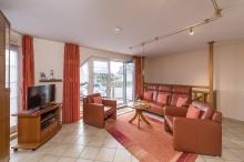 Wohnzimmer mit Couch, Schrankbetten und Zugang zu Balkon und Souterrain